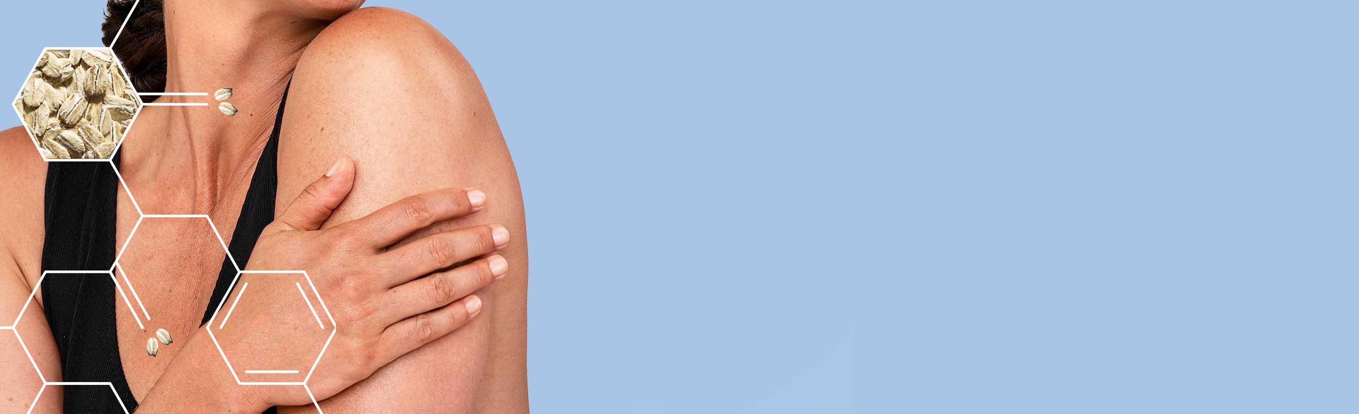 gros plan de la main d'une femme posée sur son bras sur fond bleu pâle