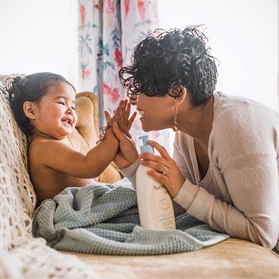 mère appliquant la lotion pour bébés aveeno sur son enfant
