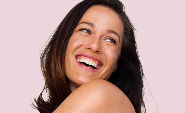 woman against a pink background smiling