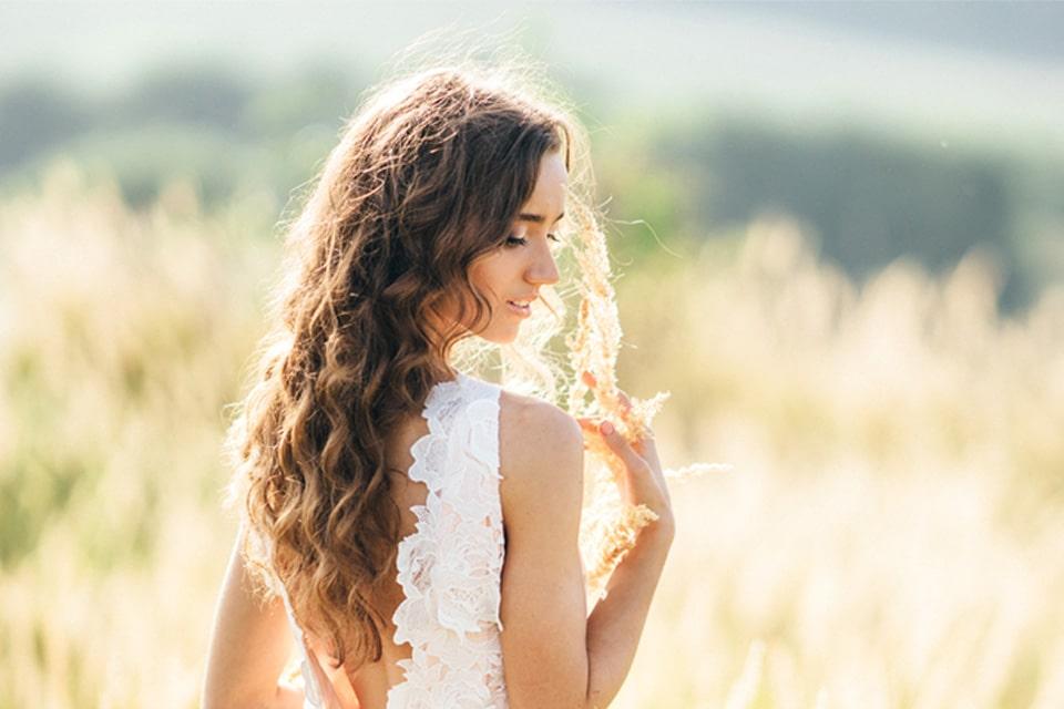 femme aux longs cheveux bruns ondulés posant la main sur son épaule