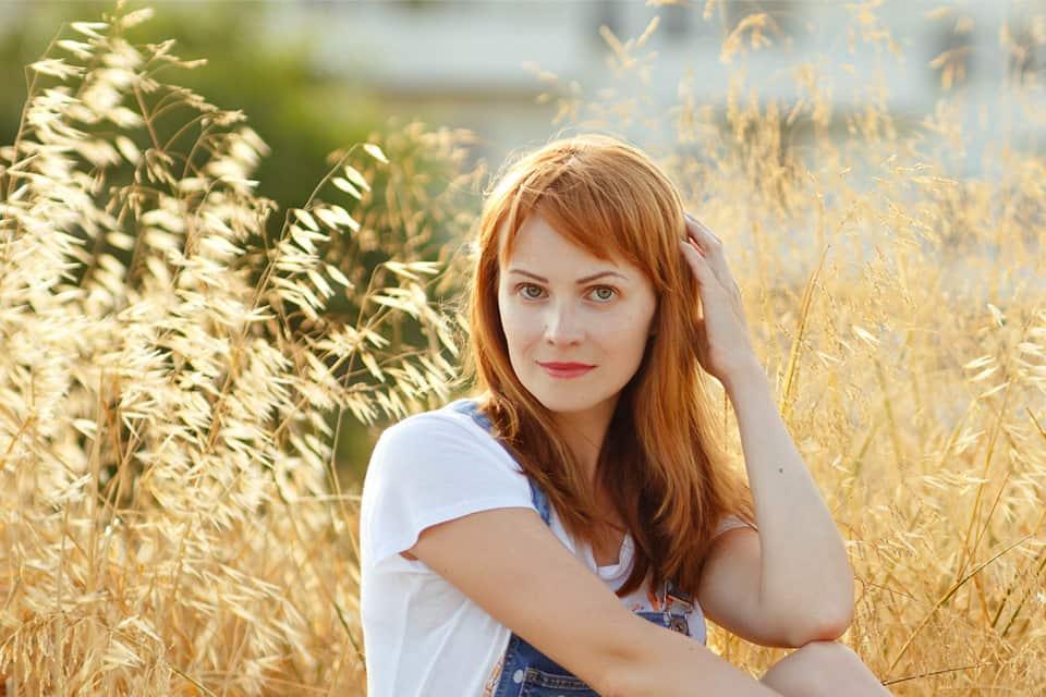 femme aux cheveux roux portant un t-shirt blanc posant la main sur ses cheveux