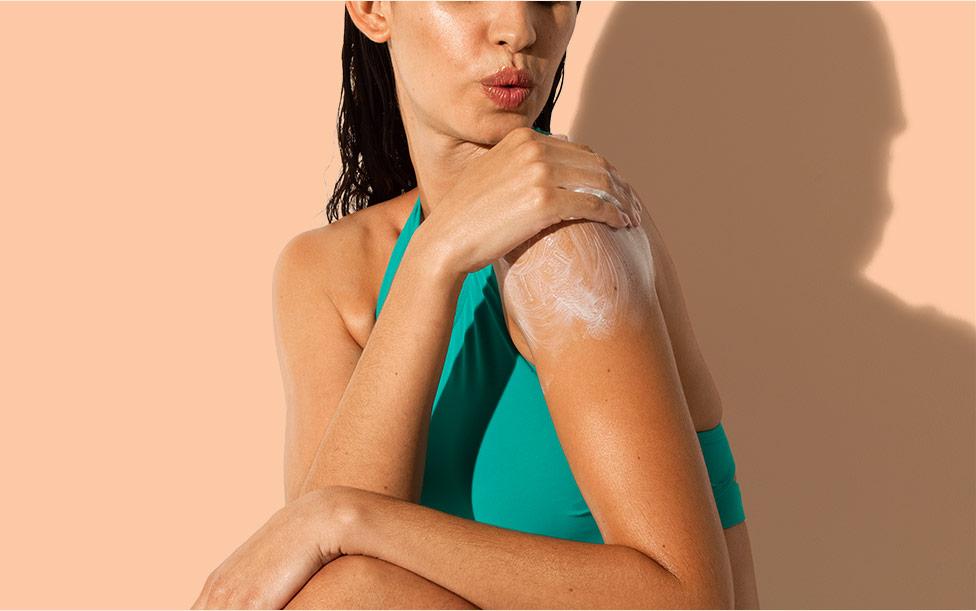 woman applying aveeno sunscreen lotion on her shoulder
